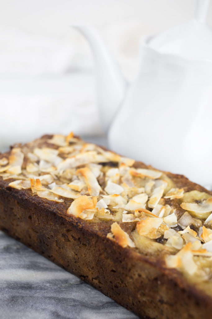 Top of coconut banana bread showing the shaved coconut and sliced bananas