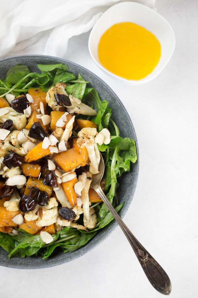 Birdseye view of pumpkin and cauliflower salad with dates and almonds on top in blue bowl Orange vinaigrette in small white bowl to the side.