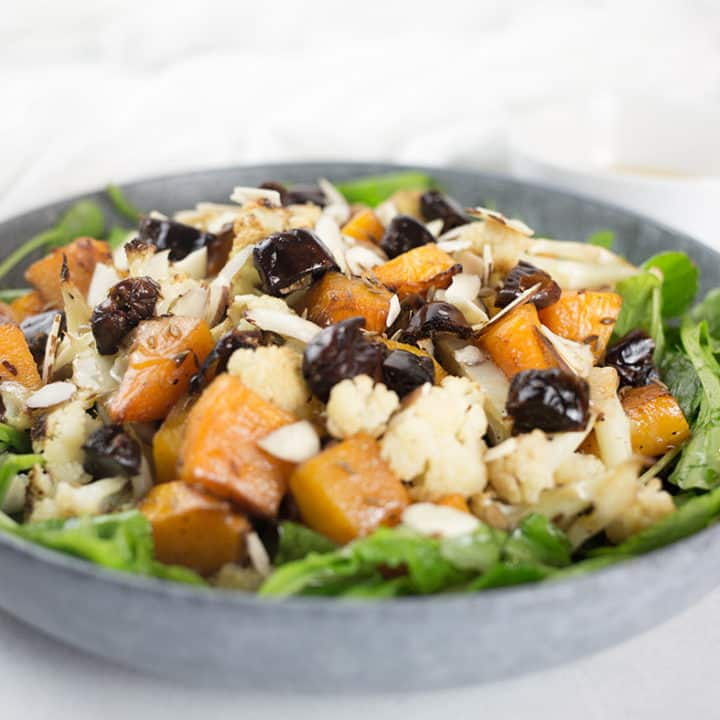 Close up of pumpkin and cauliflower salad in blue bowl with white background.