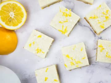 Lemon squares on marble background with lemon and teapot behind.