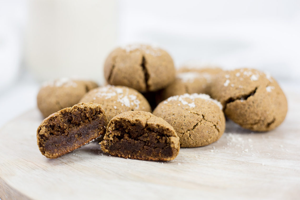 Ginger molasses cookies on board with one cute open.