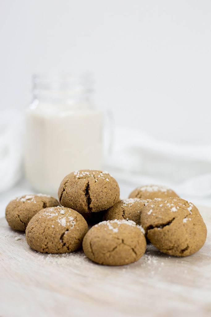 Ginger Molasses Cookies on board with glass jug of milk behind. White background.