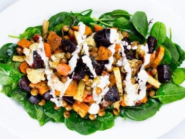 Roasted vegetable salad on plattter on white background.
