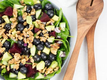Spinach and Blueberry Salad in bowl with serving spoons to the right.