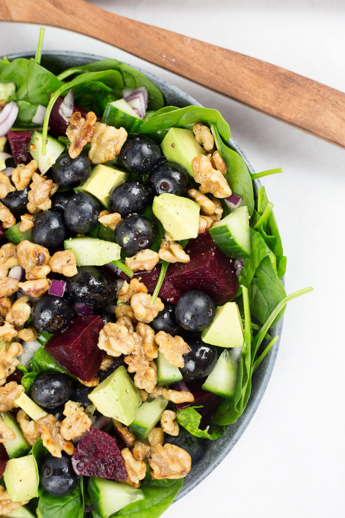Close up of spinach, blueberry and avocado salad showing half the blue bowl with brown server across the top.