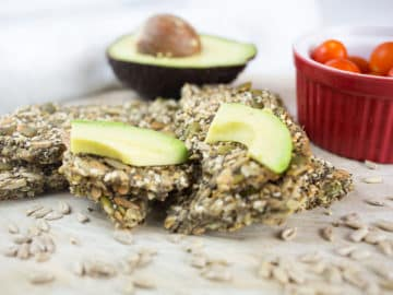 Close up of seed crackers with chopped avocado and red bowl of tomatoes in background.