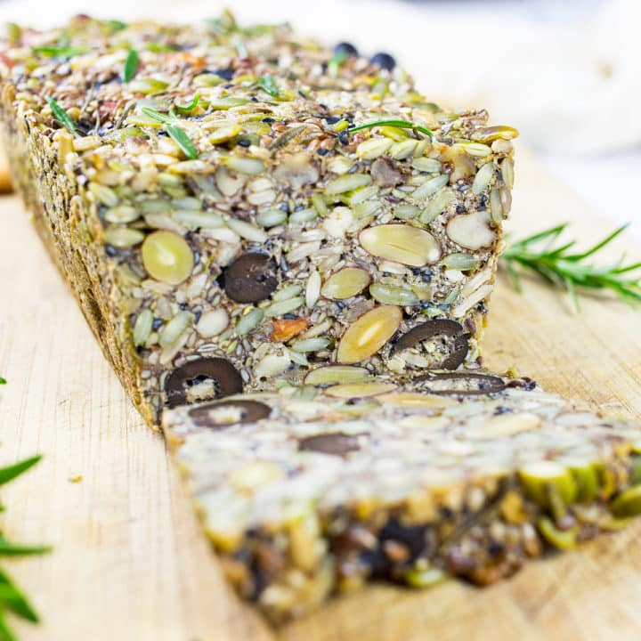 Paleo Nut and Seed Bread Sliced on a chopping board with roasemary in the background.