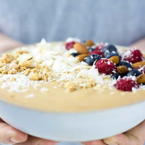 Peach Smoothie Bowl being held by a ladies hands.