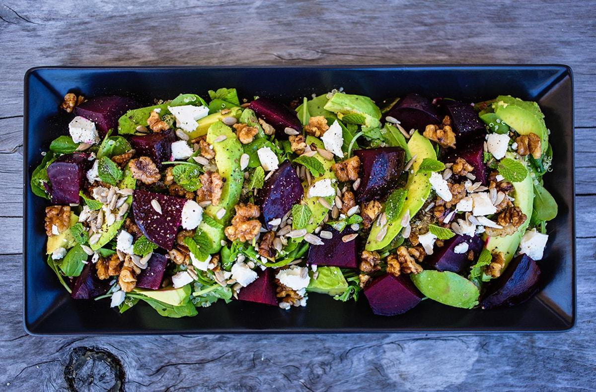 Birdseye view of beetroor, avocado and feta salad on black platter on wooden table.