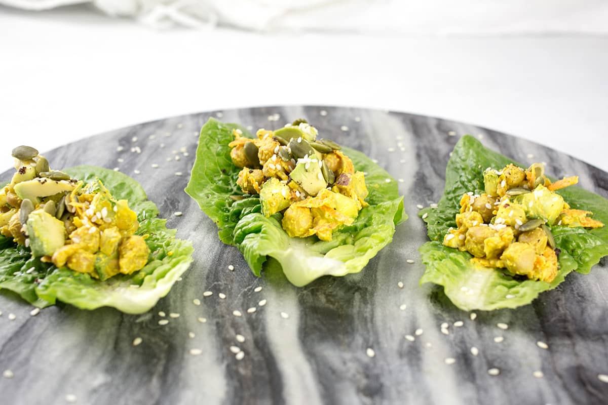 Lettuce wraps filled with chickpea salad and avocado and seeds sprinkled on top on marble platter.