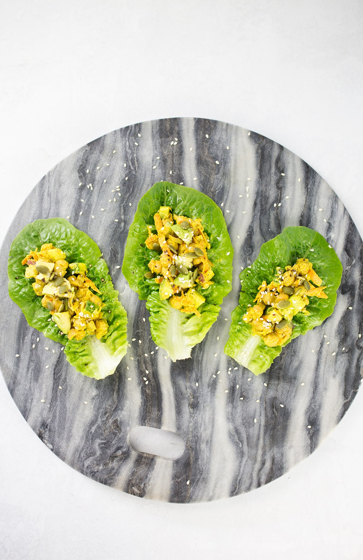 Birdseye View of Curry Chickpea Lettuce Wraps on marble platter. 3 lettuce wraps.