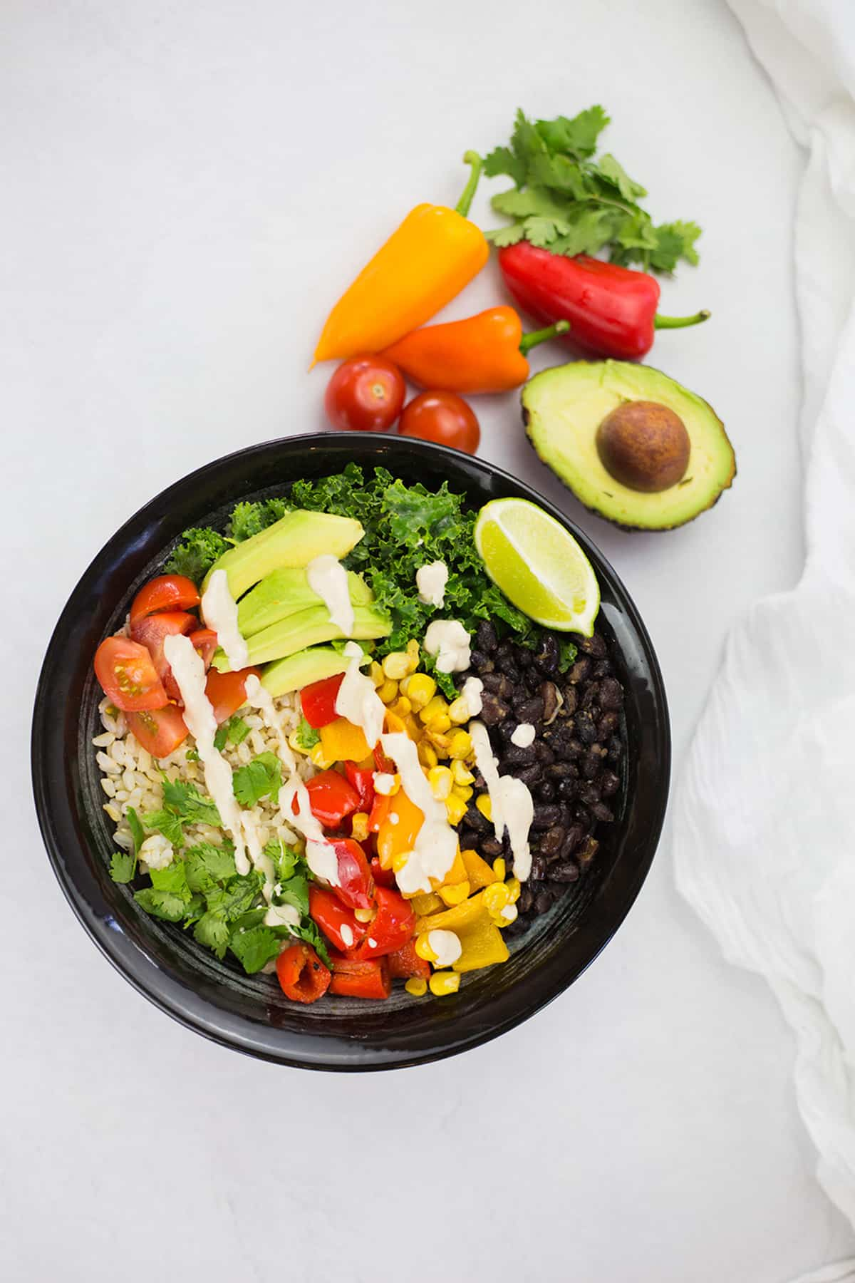 Birdseye view of vegan burrito bowl in black bowl on white background with vegetables in the background.