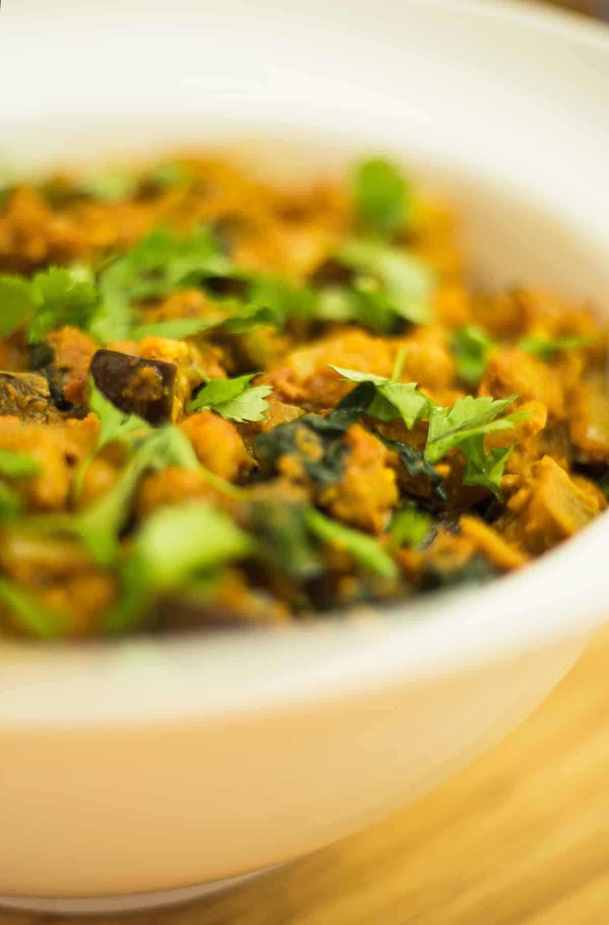 Close up of aubergine and chickpea curry in a white bowl on wooden background.