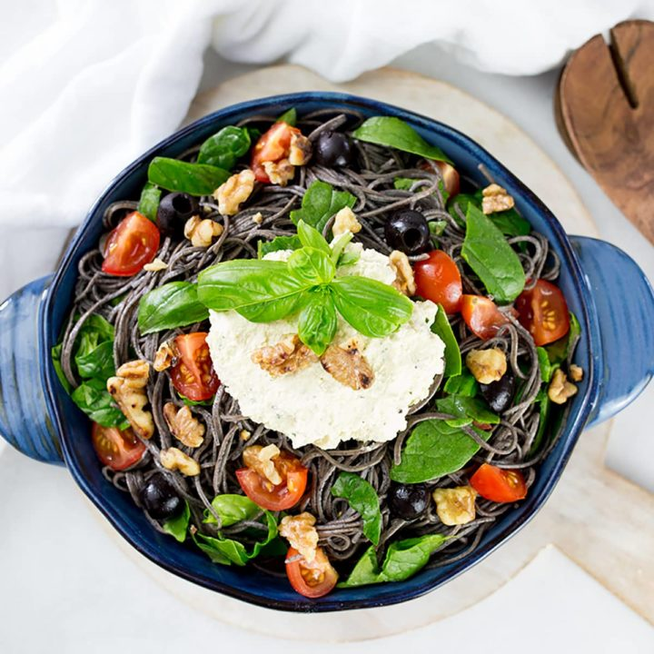 Birdseye view of black bean spaghetti in blue serving dish with wooden servers to the side.