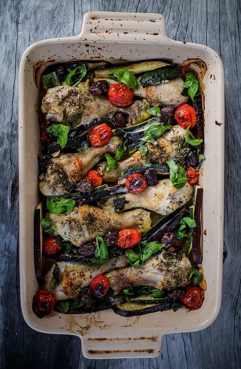 Mediterranean Chicken Bake in baking dish on wooden background.