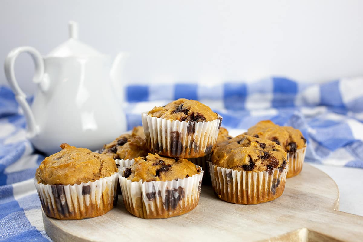 Sweet Potato Chocolate Chip Muffins on chopping board with blue cloth and white teapot behind.