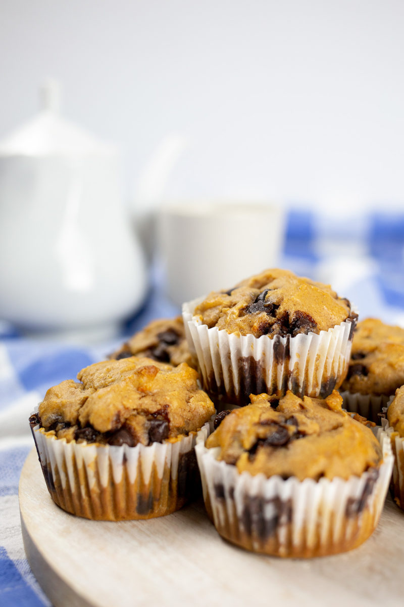 Close up of sweet Potato Chocolate Chip Muffins with blue and white cloth behind and teapot and white mug.