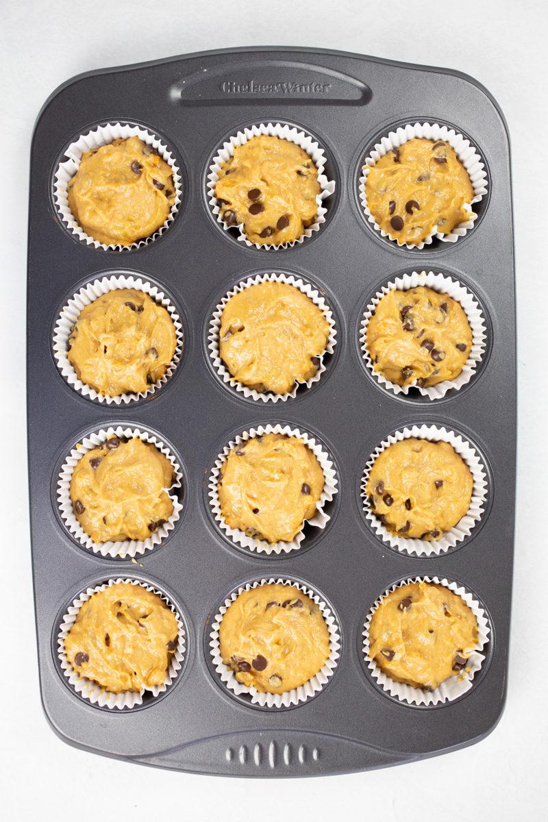 Muffin batter in prepared muffin tray.