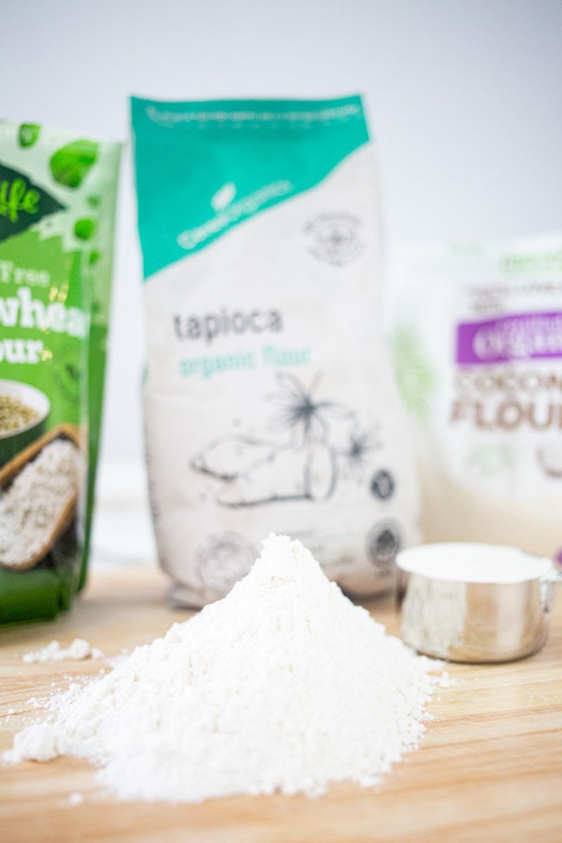 Pile of gluten-free flour on board with other flours in the background.