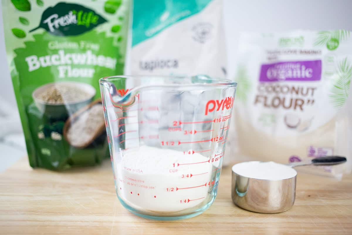 Selection of gluten free flours with flour in a jug and some in a measuring cup.