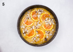 Process shot 5, cake batter in cake tin with sliced oranges and almonds on top.