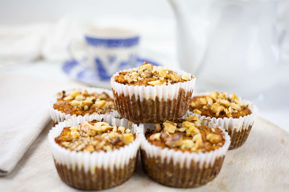Pumpkin banana muffins on board with teapot and blue and white cup and sauce behind.